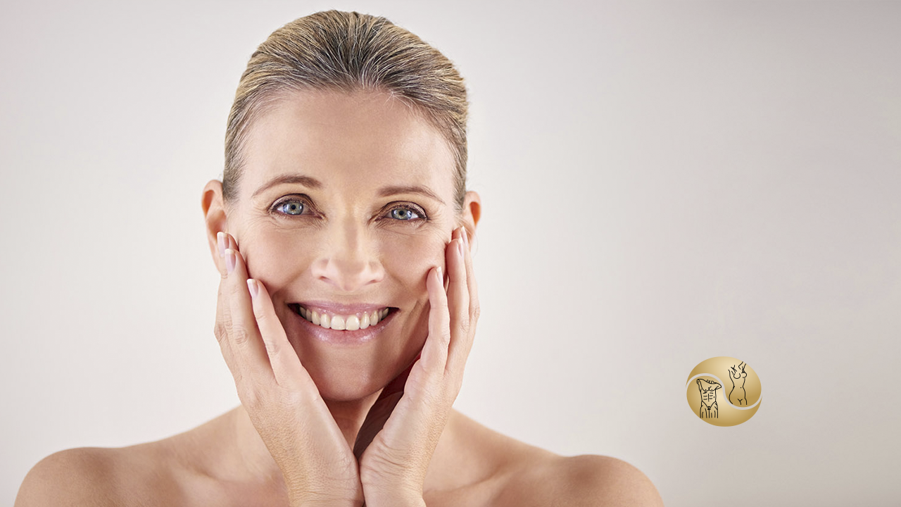 Bichectomia - na imagem há uma mulher sorrindo com as mãos no rosto.
