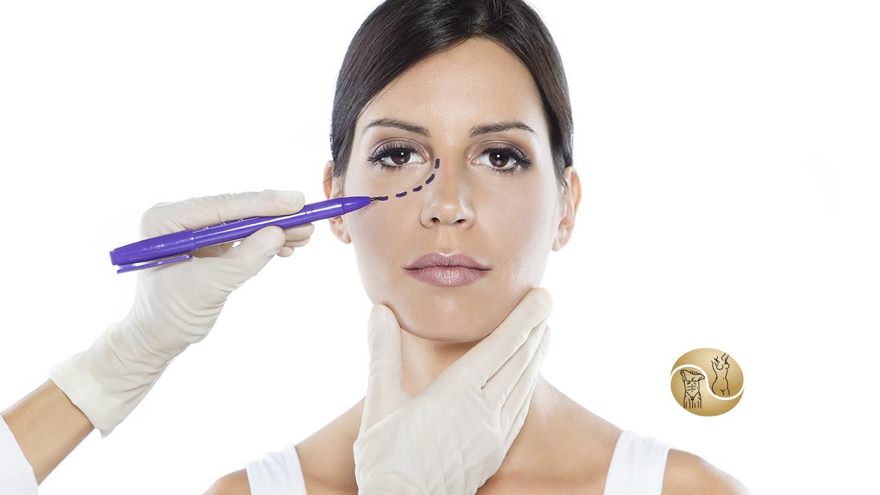 blefaroplastia - na imagem aparece o rosto de uma mulher, com duas mãos com luvas brancas de outra pessoa marcando seu rosto na região dos olhos.